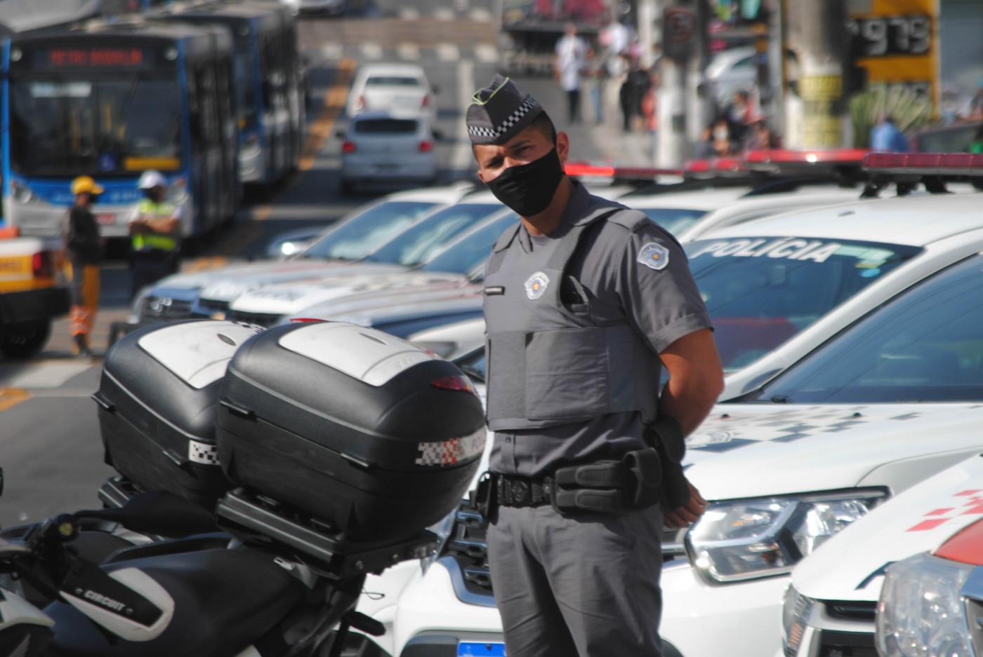 Policial militar usa uniforme da corporação e máscara de proteção preta