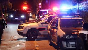 À noite, policiais travam rua com uma viatura (outra está estacionada) para apurar uma ocorrência