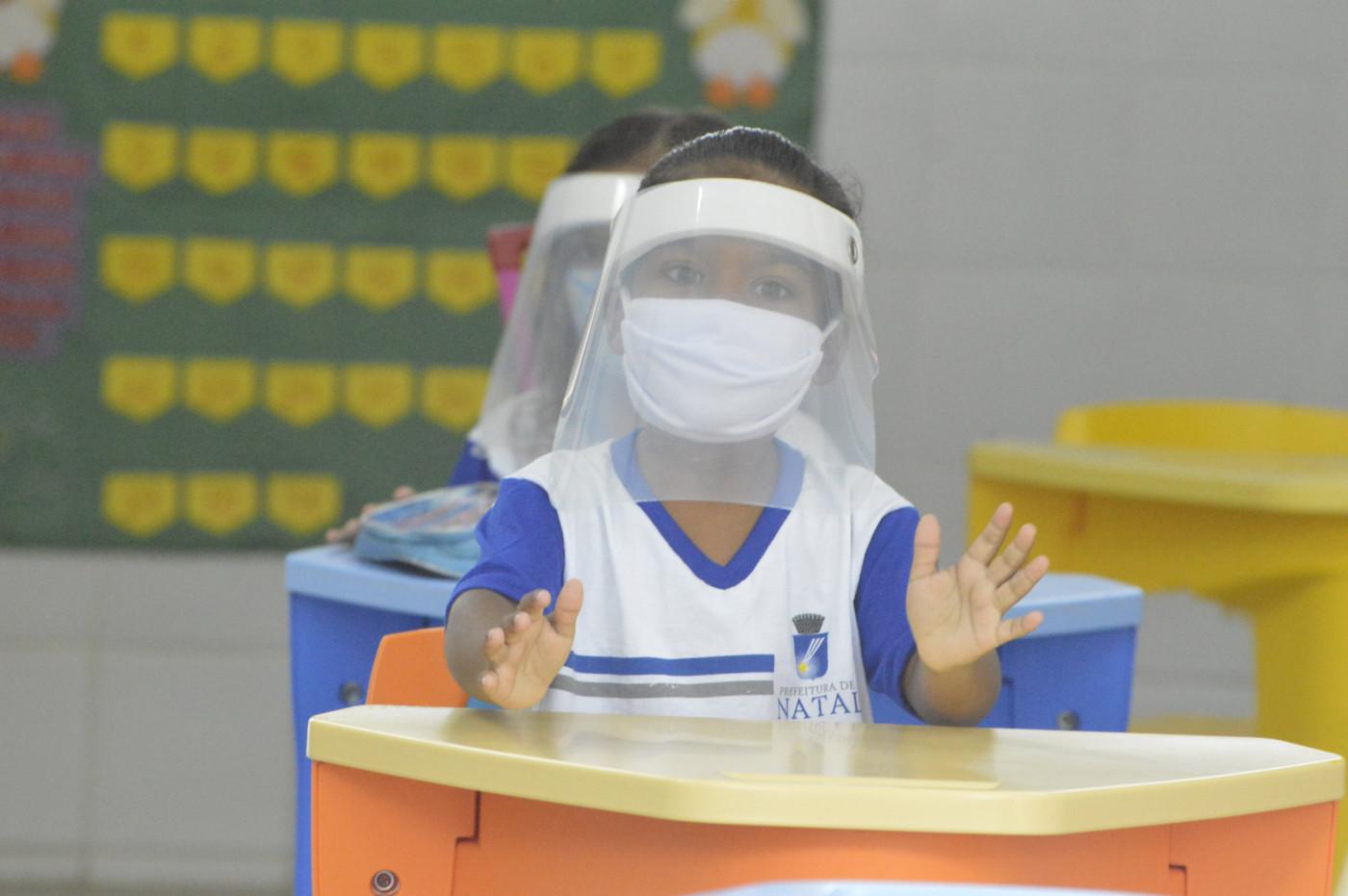 Aluna usa máscara de proteção e face shield dentro de sala de aula