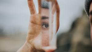Pessoa segurando um pedaço de espelho quebrado. Dá para ver só um olho.