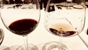 Duas taças de vinho pouco cheias, uma com vinho tinto outra com vinho branco em cima de uma toalha de mesa branca