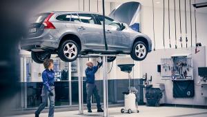 Automóvel é suspenso enquanto dois mecãnicos, um homem e uma mulher, observam
