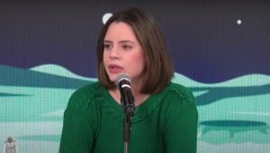 Zoe Martinez, mulher branca de cabelos curtos castanhos e blusão verde de lã, fala ao microfone