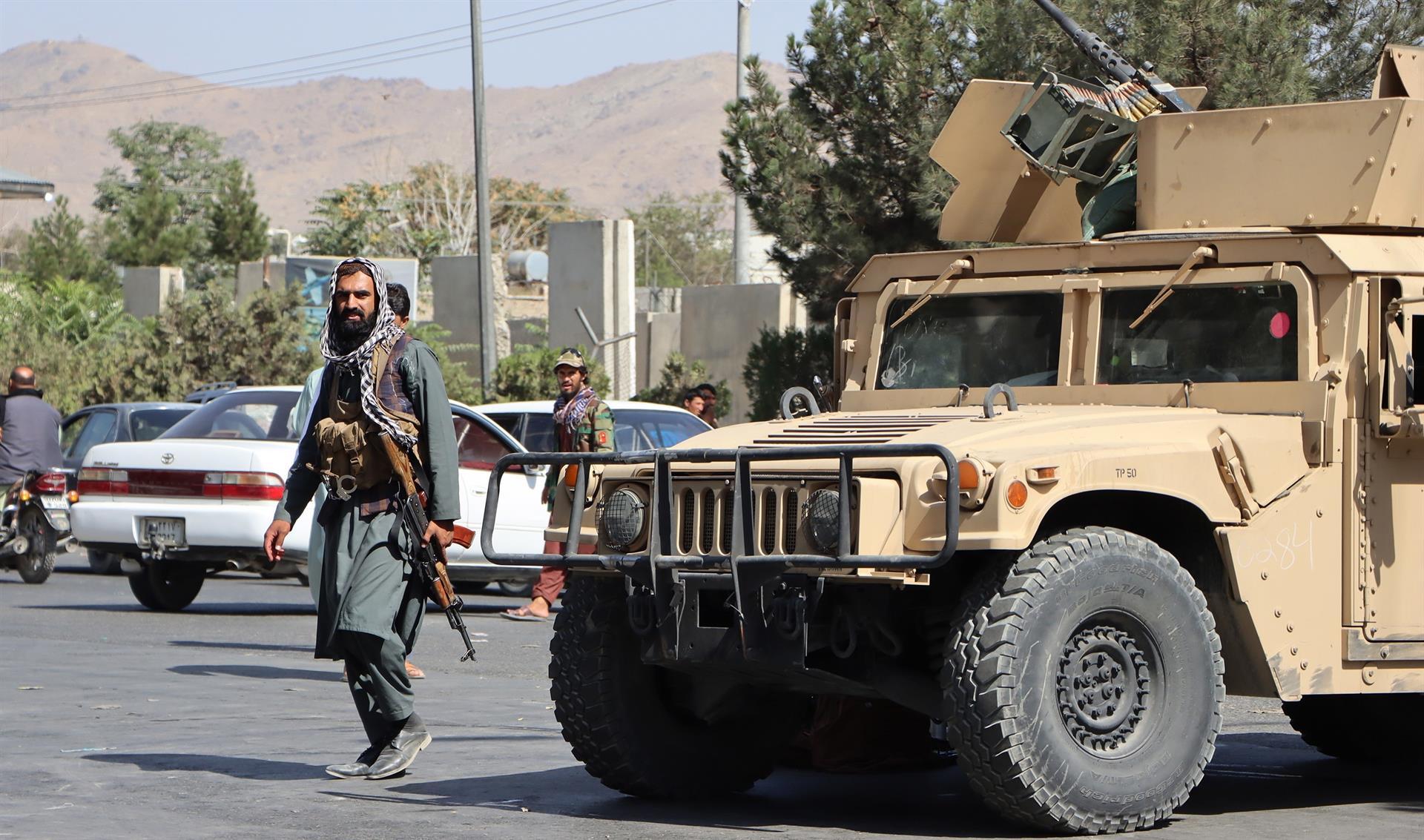 Soldado talibã andando na rua com arma em punho