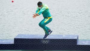 """Saltando com os joelhos flexionados e os braços esticados, quase juntos, Isaquias Queiroz imita o famoso golpe kamehameha, do anime """"Dragon Ball"""" no pódio olímpico"""