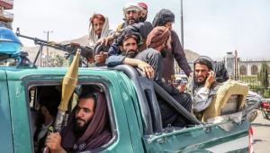 Combatentes talibãs são vistos na traseira de um veículo em Cabul,