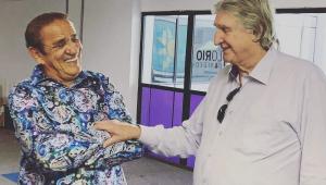 Sérgio Reis, de camisa clara de manga comprida, toca o braço direito de Zé Ramalho (que está cruzado com o esquerdo); os dois riem