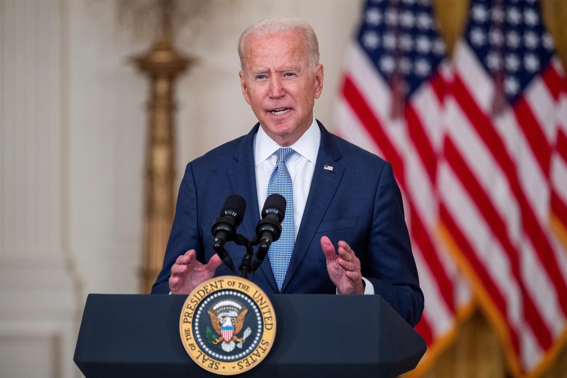 Joe Biden falando em microfone diante de bandeiras dos Estados Unidos