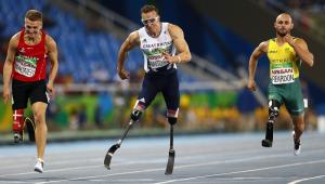 Três atletas amputados disputam a prova dos 100 m: um britânico, de branco, que lidera em uma pista central, um dinamarquês de vermelho, à esquerda, e um australiano, de amarelo, à direita