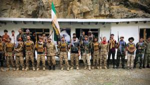 Grupo de homens armados diante de uma casa