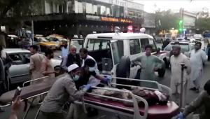 Pessoas amontoadas em cima de uma maca com alguém deitado e uma ambulância