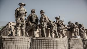 Um grupo de soldados com uniformes militares lado a lado de costas em cima de uma espécie de muro