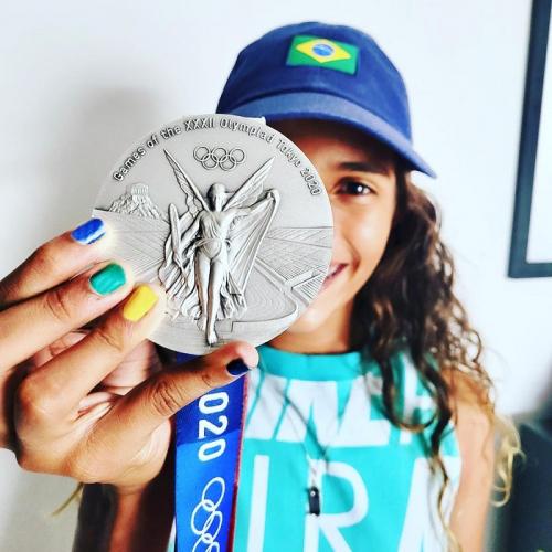 Rayssa Leal, de boné azul e unhas pintadas de diferentes cores, estende a mão direita e exibe a medalha de prata, que aparece em primeiro plano na imagem