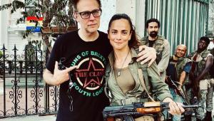 Vestida como sua personagem, com uma metralhadora presa a corpo por uma alça, Alie Braga posa para foto com o diretor James Gunn, que coloca o braço esquerdo sobre seus ombros