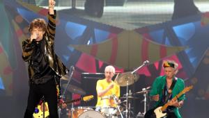 À frente do palco, Mick Jagger canta segurando o microfone com a mão direita e ergue o braço esquerdo, enquanto, atrás dele, o guitarrista Keith Richards e o baterista Charlie Watts tocam seus instrumentos