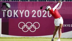 A golfista sul-coreana Koh Jin prepara um arremesso com um banner de Tóquio 2020 ao fundo