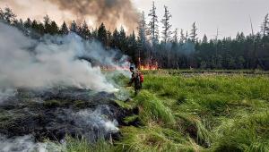 bombeiro controlando fogo na Rússia