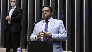 Deputado dando discurso na tribuna. Usa terno cinza e está falando ao microfone com as mãos juntas
