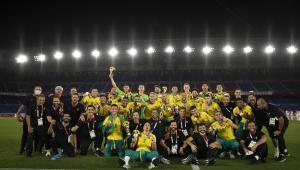 Jogadores da seleção brasileira se amontoam, com alguns agachados e outros em pé, em foto posada após o título olímpico