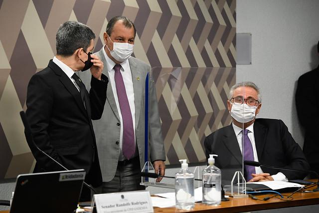 Randolfe Rodrigues e Omar conversam em pé (e usando máscaras) durante sessão da CPI, enquanto Renan Calheiros ouve a conversa do aliados sentado em seu lugar