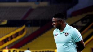 Com uma camisa branca do Fluminense, Roger Machado observa o jogo à beira do campo