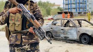 soldado com arma do lado de carro explodido