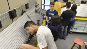 Alunos mexendo em uma barra de ferro durante um curso profissionalizante na Etec