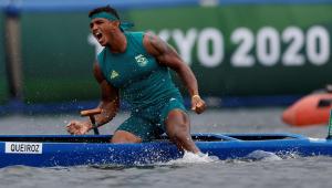 Sentado na canoa, mas com as pernas na água, Isaquias, vestido de verde, solta um grito após ganhar o ouro