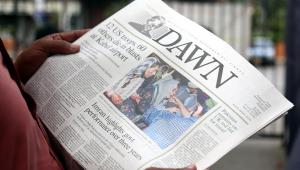 Pessoa lendo jornal com manchete mostrando ataques no afeganistão