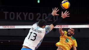 Em disputa na rede, Wallace ataca e o argentino Palacios, de costas para imagem, exibindo o número 13, tenta o bloqueio com as duas mãos estendidas