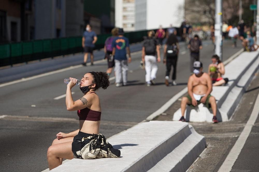 Mulher de top e saia, sentada no canteiro central do Minhocão, bebe água; há um homem de boné e sem camisa a alguns metros dela, e um grupo de pessoas andando de costas para ela em uma das vias