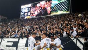 Seis jogadores do Corinthians festejam um gol perto da arquibancada, torcedores fazem festa e placar mostra Corinthians 1 x 0 São Paulo