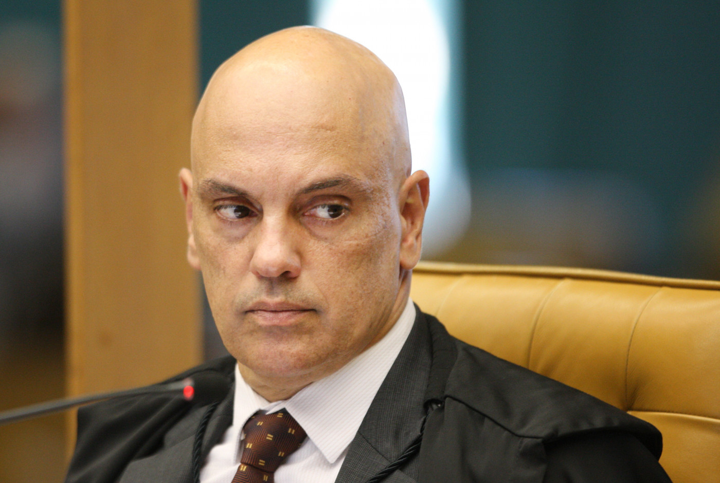 Ministro Alexandre de Moraes olhando com os olhos de canto, sentado em cadeira amarela, com terno vermelho, camisa branca e gravata bordô com bolinhas