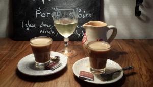 Taça de vinho branco cheia na metade e duas xícaras de café