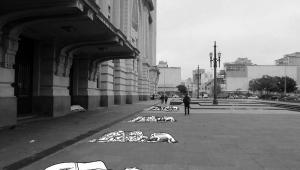 Imagem em preto e branco em um espaço público com desenhos que representam pessoas em situação de rua