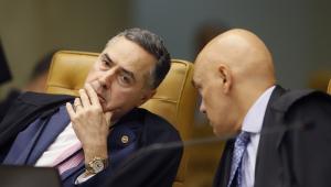 Luís Roberto Barroso estica o pescoço para ouvir Alexandre de Moraes, que está à sua esquerda (ambos estão de toga e em trajes sociais)