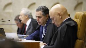 O ministro do STF Alexandre de Moraes olha para o seu celular, enquanto o colega Luís Roberto Barroso se concentra em seu notebook; ambos estão sentados em uma bancada, e próximo a eles, desfocado, aparece Ricardo Lewandowski