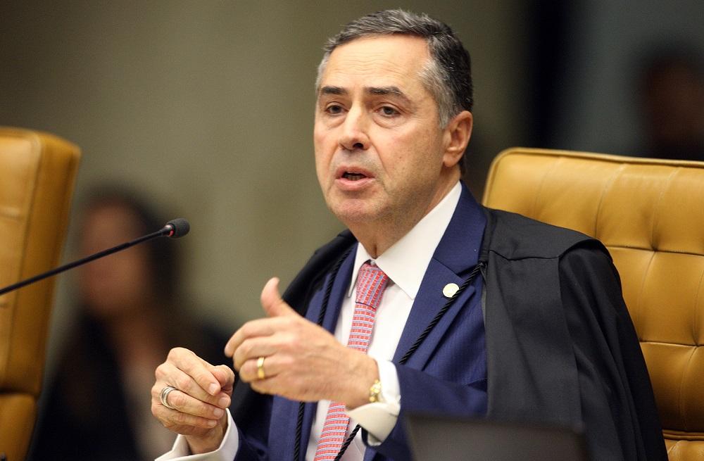 Ministro Barroso falando em sessão no STF. Homem de mais idade, cabelos grisalhos, terno, toga preta e gravata rosa sentado em poltrona amarela