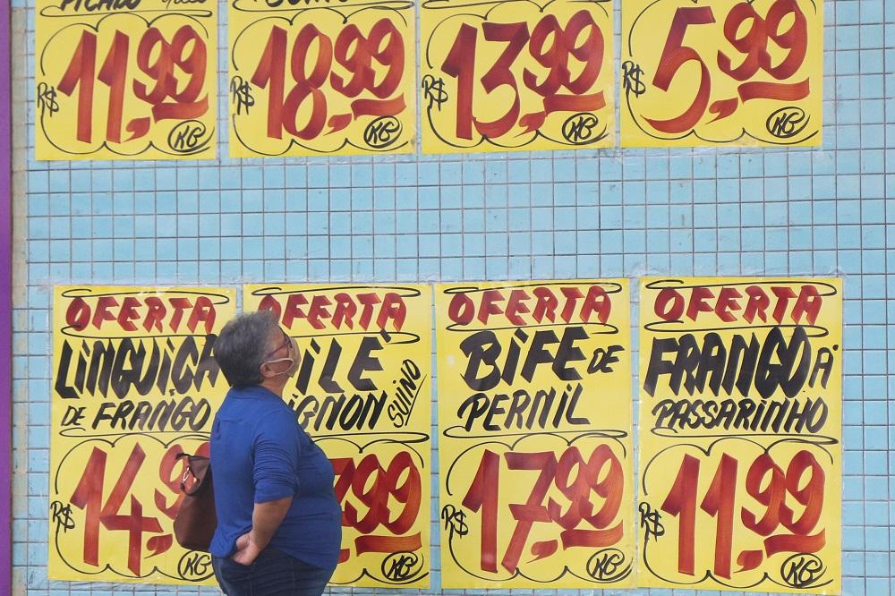 Mulher olha para parede de açouge em que cartazes com os preços das carnes estão fixados