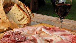 Vários tipos de presunto e um pão em primeiro plano e uma taça de vinho atrás