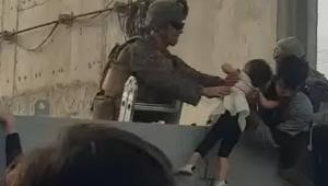 Criança sendo passada por cima de muro no aeroporto de cabul
