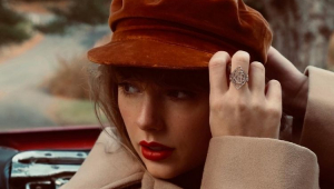 Taylor Swift ajeitando uma boina vermelha