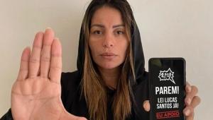Walkyria Santos com a mão para frente indicando parar parar e com um celular na mão