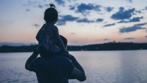 Homem com criança nos ombros de costas olhando para um rio