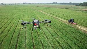 Imagem aérea mostra um drone sobrevoando um extenso campo agrícola, por onde passa um trator