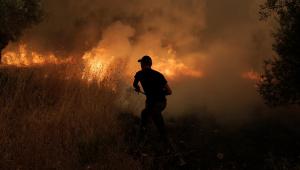 bombeiro tentando controlar incêndio na Grécia