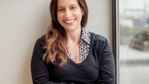Fabiana Guitierrez, mulher branca, na faixa dos 30 anos, posa para foto sorrindo, sentada e com as mãos nas pernas