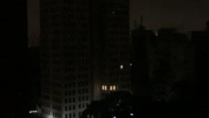 Vista de uma janela de predios e casas sem luz em São Paulo
