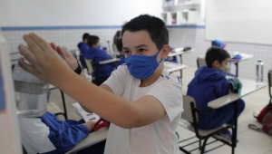 Menino usa máscara de proteção na escola e pega álcool gel