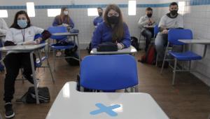 Carteira escolar aparece vazia e alunos retomam aulas presenciais com distanciamento